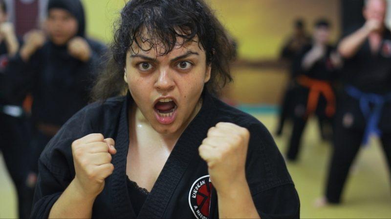 Eine junge Frau trainiert Karate.